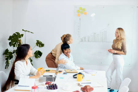 Young beautiful business coach teacher team leader represent her business strategy to co-workers in white office, multi-ethnic group of listeners Stock Photo