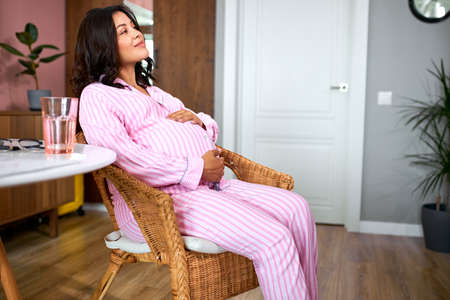 adorable pregnant woman in domestic wear dream to give birth, think and ponders what her future baby will be like. tranquil relaxation. mom to be.
