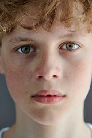close-up portrait of redhead freckled teenager boy with bewitching look, caucasian boy with green eyes confidently looks at camera