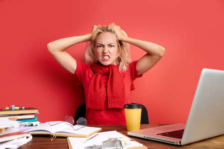 young stressed caucasian female working with computer laptop in frustration, depression. she has stress problems and despair at work, isolated on red background
