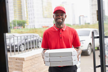 smiling afro american deliveryman with pizza in hands, going to give it for clients, look at camera wearing red uniform