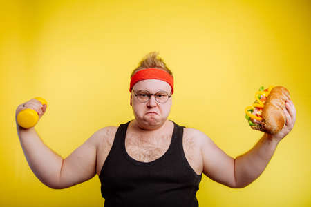 big fat hungry man show biceps with hamburger and dumbbell Stock Photo