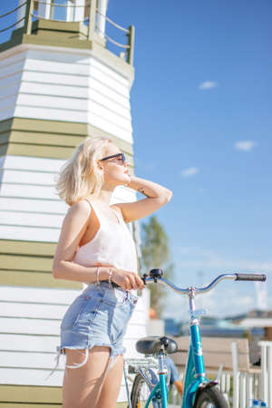 Sports lifestyle. Woman with bicycle on the on the sea pier while standing near cafe decorated as viewing place. Outdoor summer portrait of caucasian girl cycling during her holiday or vacation