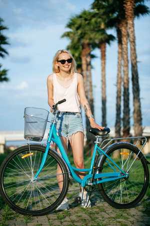 Tourist female wearing sunglasses taking a tour to exploring around countryside with palm alley using cruiser bicycle at summer sunny weather.