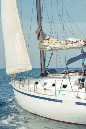 Sailing. Yachting in Mediterranean Sea. Sailboat with white sails on calm sea in sunny weather.