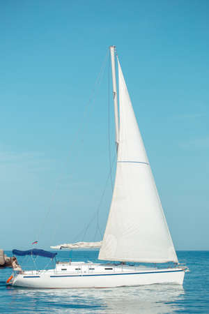 Sailing ship yacht with white sail in the open sea heading to neapolis coast