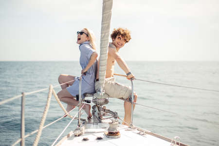 Young european romantic couple smiling at camera while sitting at bow of boat, back to back, enjoying their holidays. Beautiful sea views with copyspace. Hapiness, People Relation, Sea vacation