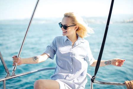 Beautiful joyful female tourist having fun during marine cruise on comfortable pleasure boat or yacht.