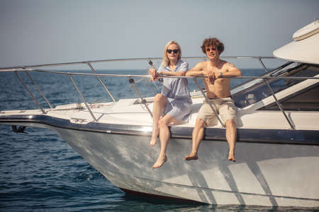 Just married couple decide to have a sea trip on summer holydays. Man rent a sailing boat and getting a good ride along Black sea Coast together with a girlfriend Stok Fotoğraf