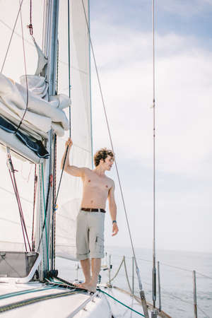 Young half-naked crew member man working aboard the private yacht taking part in annual marine competition Banque d'images