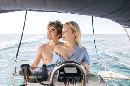 Young male captain teaching his attractive blonde girlfriend driving luxury pleasure yacht , summer vacation concept