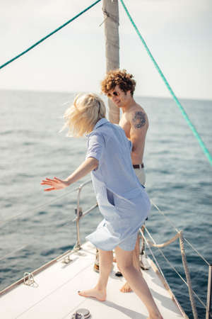 Blonde girl in company with her friend stand on bow of a white yacht, while the curly man helps her, both being in good mood.