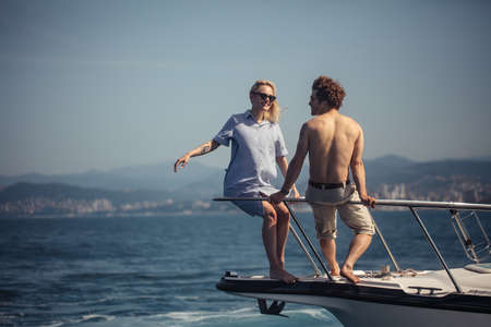 Romantic vacation and luxury travel. Young loving couple sitting on the feed of modern boat, looking at sealine. Sailing the sea.