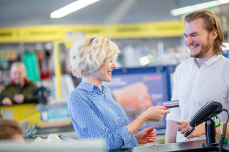 Blonde attractive woman at the supermarket checkout, she is paying using a credit card, shopping and retail concept.