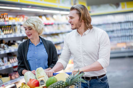 Positive family customers with full trolley of healthy organic vegetables and fruits in grocery store during weekly food shopping