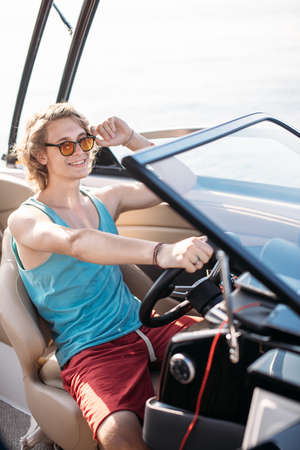 Smiling young handome man with blonde curly hair navigating speed motorboat in Caribbean sea Archivio Fotografico