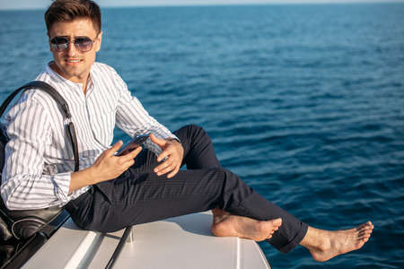 Positive caucasian freelancer with backpack over his shoulder spending resttime at sea journey, enjoys sunset from yacht.