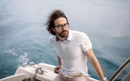 Portrait of positive adult caucasian bearded tourist taking not far-avay sea journey on luxury white yacht in Caribbean sea