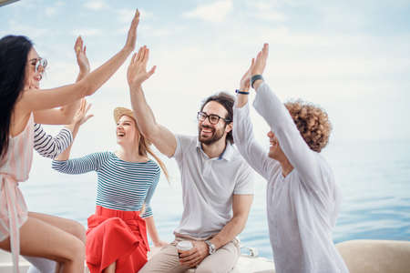 Group of friends, dressed in casual cloth, giving high five on a fashionable yacht - Happy people having a fancy party on a luxury boat