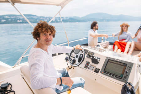 Young handsome curly captain navigatong sailing boat and looking at camera, group of joyful people chilling on deck over sea background Reklamní fotografie