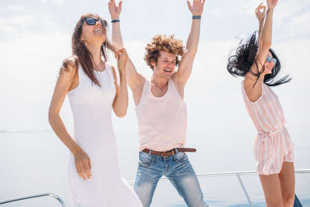 playful , caucasian friends dancing on a bow of yacht , hot dancing against blue sea background with copyspace . Beautifyl youngsters. Archivio Fotografico