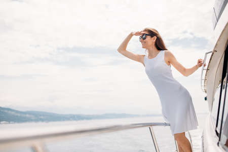 Portrait of gorgeous Caucasian brunette female model wearing sunglasses posing on modern yacht in sunny day outdoor. White dress showed her tanned skin to great advantage. lifestyle concept