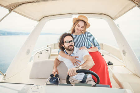 Young beautiful married couple having their honeymoon trip on a luxury sailing boat at summer Carribean Sea. Husband sitting at steering wheel and his loving young wife embracing him standing behind Stock Photo