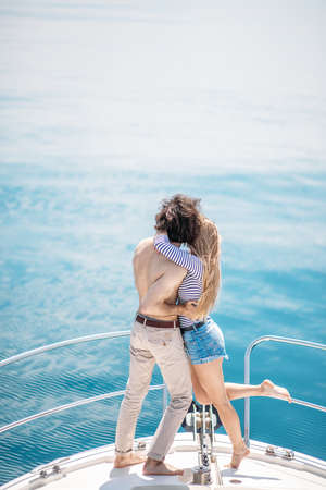 Passionate caucasian lovers dancing on bow of deck while sailing on yacht. Young couple traveling together on boat on sea, beautiful sea views with copyspace. Hapiness, People Relation Sea vacation