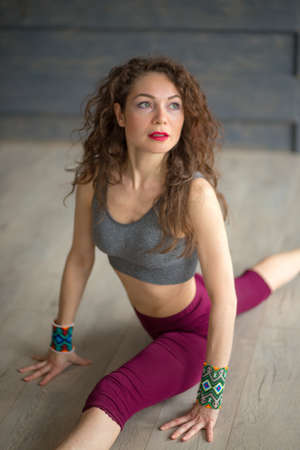 beautiful woman with loose long hair wearing sport clothing sitting on the splits in the gym