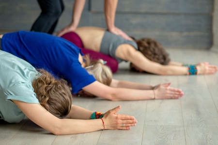 Group of caucasian adult women practicing yoga under male instructors guidance in studio.