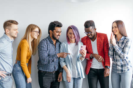 Group of Multicoloured joyful people standing against white wall. Caucasian woman with violet hair showing photos on smartphone to her diverse friends. Technology concept with young users people.