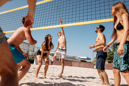 Smiling European adults, young men and women, throwing ball over net on sandy beach and laughing, enjoying vacation on sea shore. Reklamní fotografie