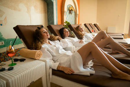 Young caucasian women in white bathrobes enjoying their vacation at spa resort. Beautiful Happy Smiling Women Enjoying Relaxing after Body Massage Treatment. Outdoors Beauty Salon.