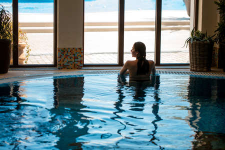 Calmness and harmony in air. Attractive young caucasian woman relaxing in spa indoor swimming-pool.
