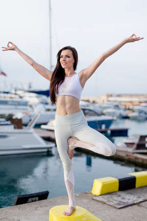 Attractive fit woman in white sportive outfit doing yoga tree pose, balancing on one leg, at pier.