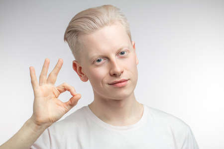 Handsome blonde man with perfect skin and cute hairstyle showing ok sign, approving quality of man s cloth he advertising. Isolated over white background with copy space Standard-Bild