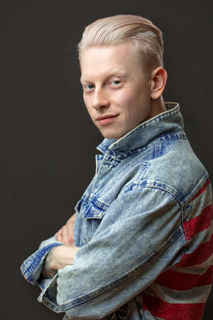 Handsome albino American male with appealing uncommon appearance, wearing casual denim cloth, looking at camera isolated over black studio, Man s Garment and Clothing. Men Beauity and fashion Concept