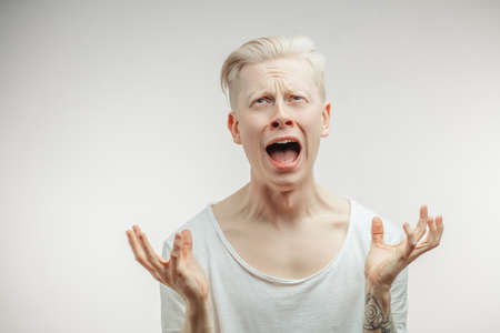 Closeup portrait upset stressed young man squeezing his head, going nuts, screaming, losing his mind, looking up isolated gray wall background. Negative emotion feeling reaction