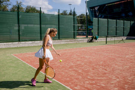 European advanced tennis female player holding serve at open court during Summer Open Championship