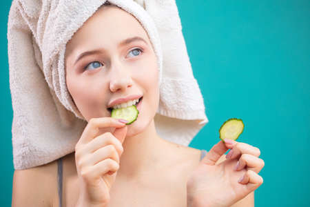 Cheerful beautiful woman with a towel wrapped around her head covering eyes with cucumber slices and looking at camera isolated over blue background