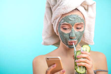 View of spa young female wearing towel on head, getting face treatment and hydration with facial mask, drinking healthy cucumber cocktail while watching new video in social media via smart phone
