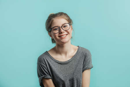 Attractive young woman in casual clothes wearing her hair in bun looking at camera with friendly charming smile over blue background with copyspace.