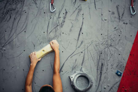 Close-up of artificial handles, hooks and bolders. Hands of climber on climbing wall