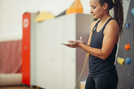 Young woman in dark grey outfit rubbing hands with with chalk preparing to workout at indoor climbing gym