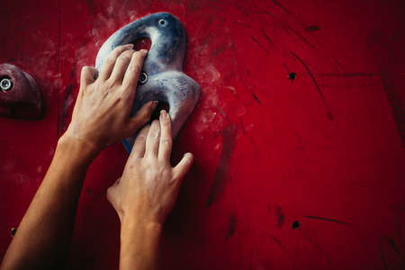 Close up of female climbers hands on red wall during bouldering. Workout in climbing gym, closeup shot