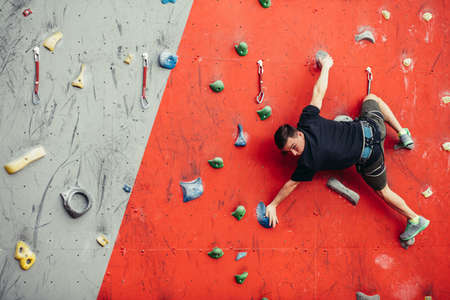 Caucasian businessman challenges new height on artificial exercise climbing wall. Hobby, Leisure, Extreme Sports and People Concept Reklamní fotografie