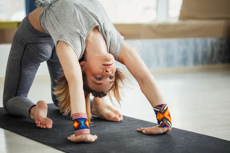 Flexible women in yoga bridge stance exercising in Urdhva Dhanurasana pose on mat at gym. Stock Photo
