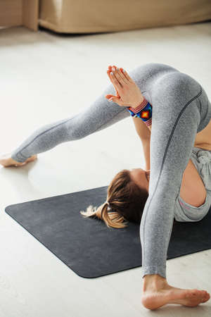 Sporty caucasian woman doing stretching yoga inverted posa lying on mat with raised up to head stretched out leggs in bright empty gym. Her arms between