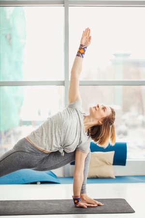 woman practicing yoga in well-litt fitness hall. Yogi female doing Extended Side Angle Pose , Utthita Parsvakonasana against floor-to-ceiling window at daytime.