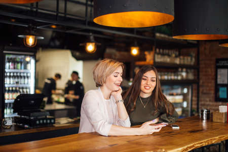 Two attractive excited young using smartphone while sitting at the cafe with cosy stylish interior